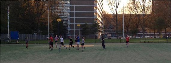 Jongeren op een korfbalveldje spelen korfbal