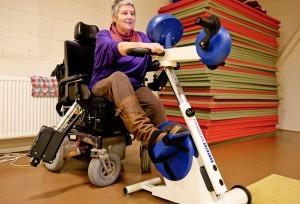 Mevrouw met beperking fiets op een aangepaste hometrainer