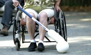 Een oudere in een rolstoel die knotsbal speelt