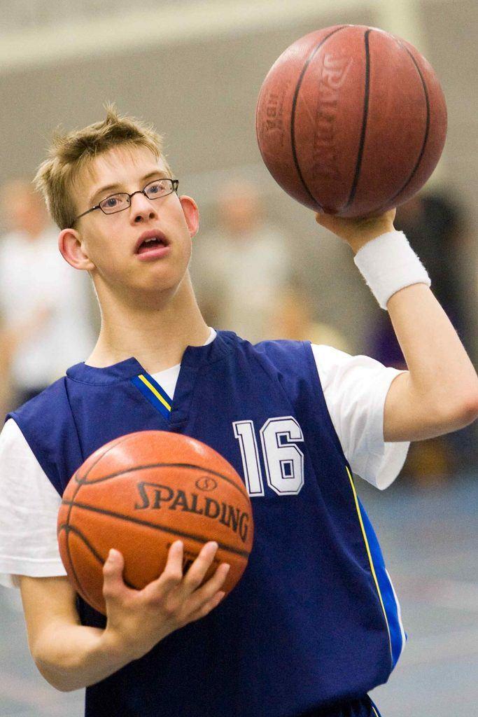 Jongen met beperking houdt 2 basketballen vast