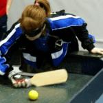 Sporter met blinddoek voor de ogen slaat met een batje een bal op een tafel