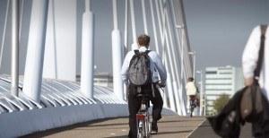 Man die over een brug fietst