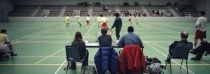 wedstrijdleiding kijkt vanachter een tafel naar een wedstrijd zaalvoetbal in een sportzaal