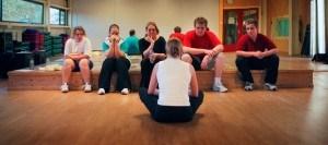 Sportdocent legt leerlingen wat uit terwijl ze op de grond zitten