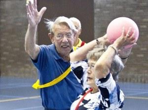ouderen doen een balspel in de gymzaal