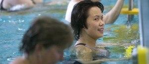 vrouw die zich vasthoudt aan de rand van een zwembad