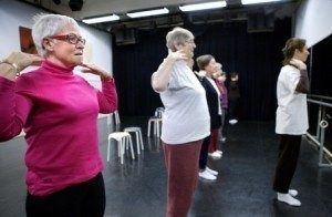 Drie oudere vrouwen doen gymnastiekoefeningen