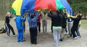 Volwassenen die een groot gekleurd doek met elkaar vasthouden