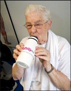 Een oudere vrouw drinkt uit een bidon