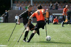 2 voetballers waarbij een been is geamputeerd die voetballen op een voetbalveld