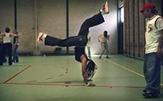 een jongere maakt een handstand in een sportzaal