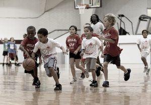Jonge kinderen die een basketbalwedstrijd spelen