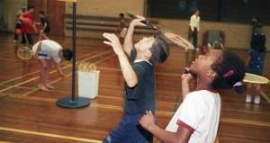 Kinderen aan het badmintonnen in de zaal
