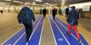 Passagiers in de hal van de RET die gebruik maken van een blauw wandelpad