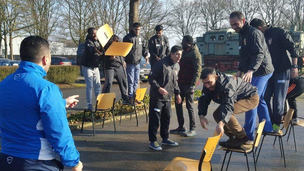 Vluchtelingen die een spel doen met stoelen