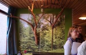 muur met fotobehang van een bos met aan de muur echte takken