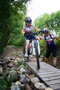 jonge wielrenner probeert over een houten bruggetje te fietsen