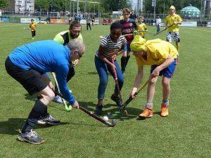 op de foto zie je ouders en kinderen hockeyen tijdens het familietoernooi