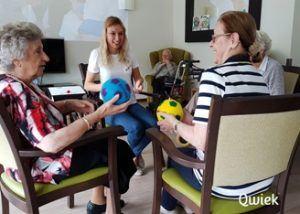 Ouderen doen samen met de begeleiding oefeningen met een bal