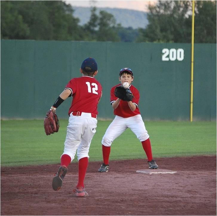 Twee jongens op een honkbal veld gooien een bal naar elkaar
