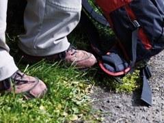 iemand met wandelschoenen aan staat naast een grote rugzak