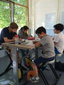 kinderen in de klas op een fiets achter een tafel