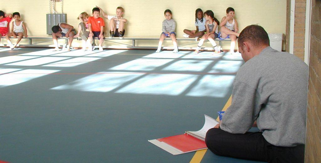 Kinderen zitten op een bankje tijdens de gymles en de gymleraar zit op de grond met een map voor zich