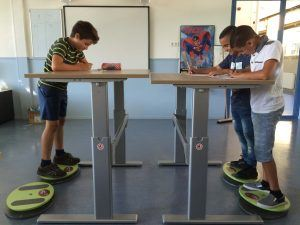 kinderen in de klas aan een sta-bureau