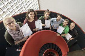 deelnemers die Het branchecertificaat in hun handen houden terwijl ze op een wenteltrap staan en naar boven kijken