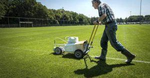 Een vrijwilliger is de lijnen aan het trekken op een voetbalveld