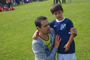 Een vader met zijn zoontje op het voetbalveld