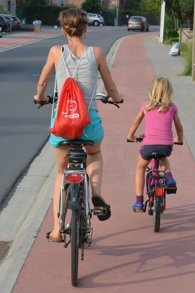 Een moeder fietst met haar kind op een fietspad