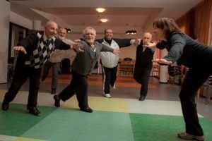 ouderen doen een balansoefening door op 1 been naar voren te leunen met de armen gespreid