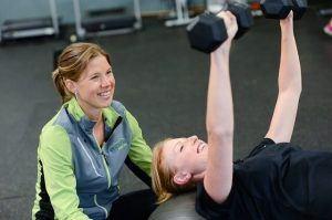 een vrouw ligt op haar rug op een trainingsbankje en doet haar armen recht omhoog terwijl ze gewichten vasthoudt