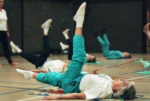 ouderen in sportkleding liggen op een matje in de gymzaal en strekken 1 been omhoog