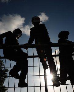 3 jongeren al hangend in een hek.