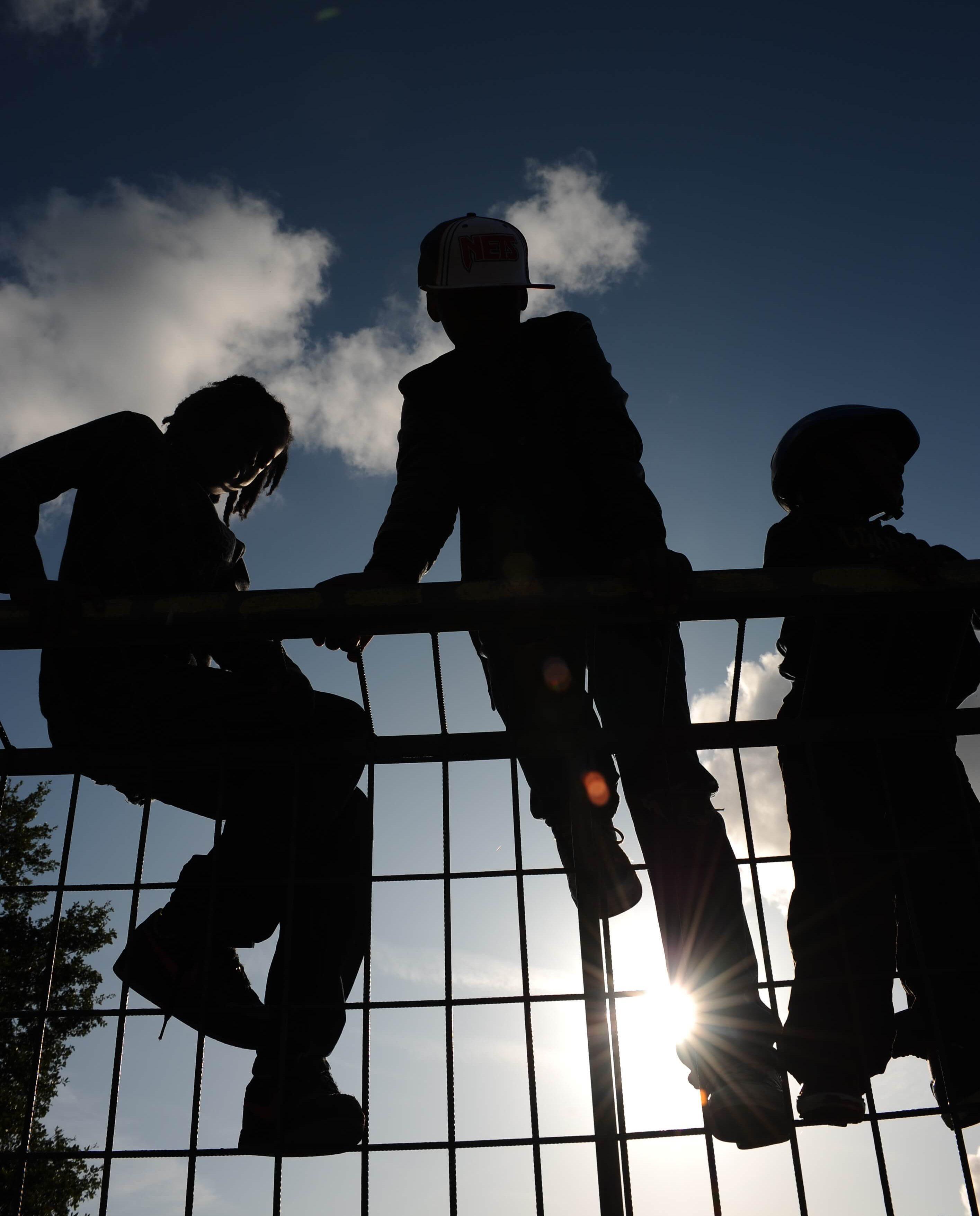 foto van Sport it in de wijk. De foto laat 3 jongeren zien al hangend in een hek.