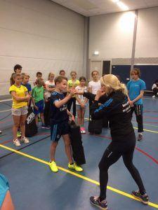 kinderen krijgen uitleg over kickboksen in de zaal