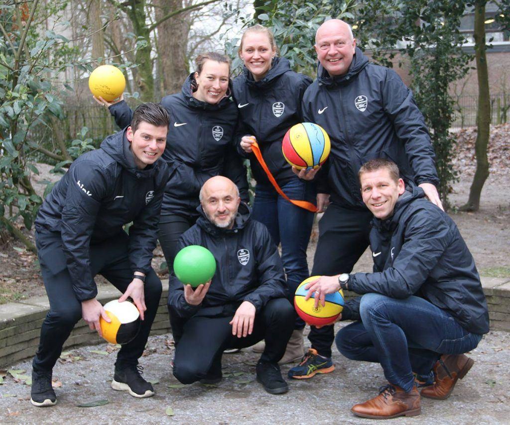 foto van team buurtsportcoaches, gemeente Soest. 4 mannen en twee vrouwen staan met een sportattribuut in een gezellige opstelling