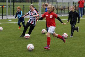 een meisjesvoetbalelftal aan het trainen in Tilburg