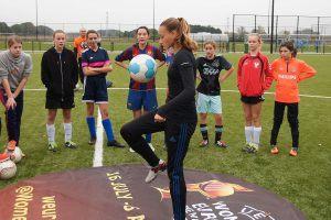een damesvoetbalelftal in Tilburg kijkt naar het hooghouden van een voetbal door een voetbalster