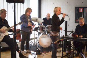 Een band is aan het spelen tijdens Kenniscafé Sport Live