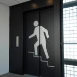 Een lift met een afbeelding van een poppetje die een trap oploopt