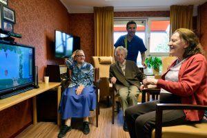 3 ouderen zitten rondom een tv in de huiskamer van een verzorgingshuis