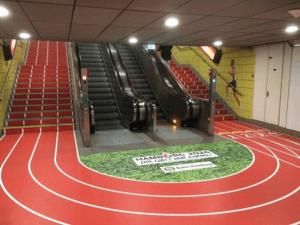 een trappenhuis met roltrap en gewone trap waarop een atletiekbaan is gemaakt om bewegen te stimuleren