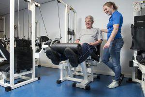 Man traint benen op fitnesstoestel met begeleider ernaast