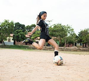 een jonge vrouw gaat een bal weg schoppen in het zand