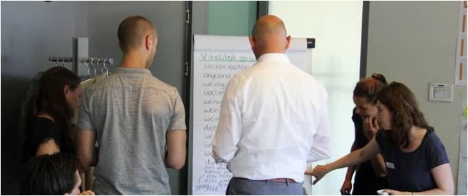 medewerkers staan bij een flipover bord en lopen de punten door die opgeschreven zijn
