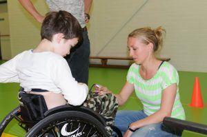 vrijwilliger helpt een jonge sporter in een rolstoel