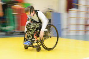 Jongen met beperking beweegt zich snel voort in een rolstoel. Hij heeft een masker op om metingen te doen